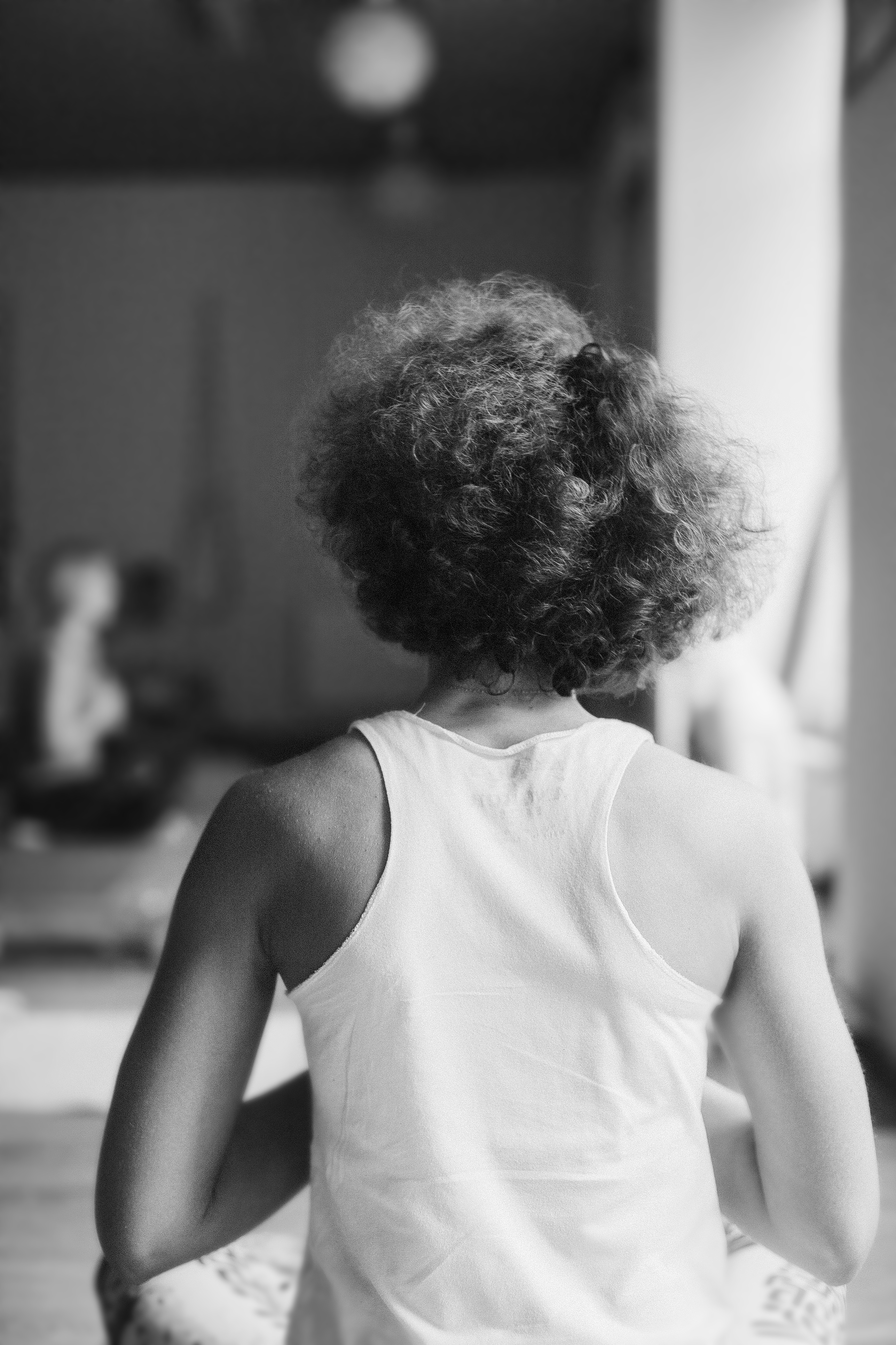 short curled hair woman from the back sitting in yoga classroom